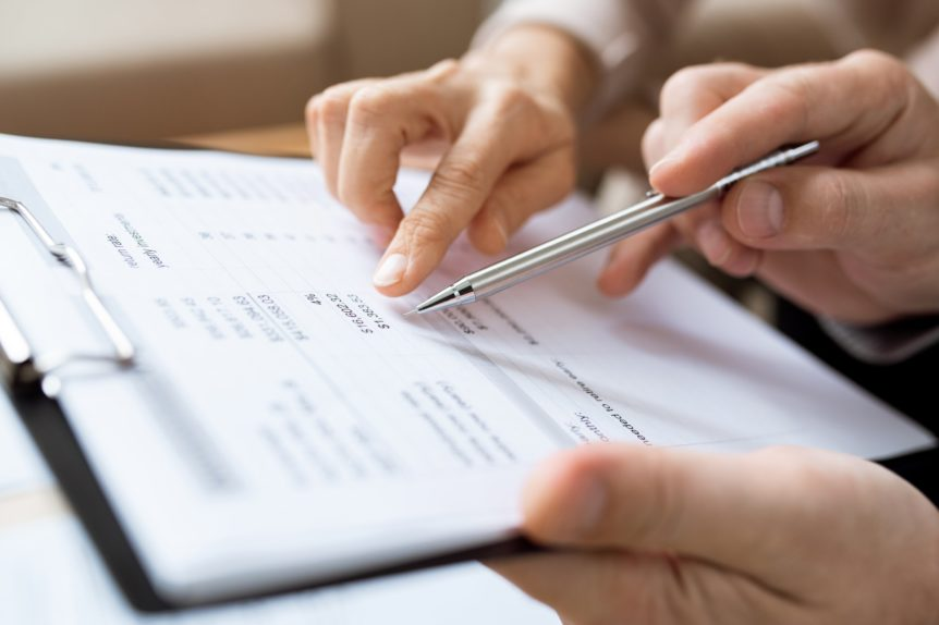 One of humans holding pen over paper while discussing financial expenses